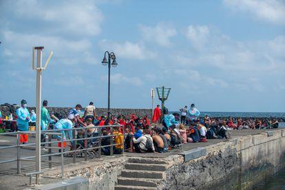 Decenas de inmigrantes son atendidos en el muelle tras llegar a Órzola (Lanzarote), este domingo.