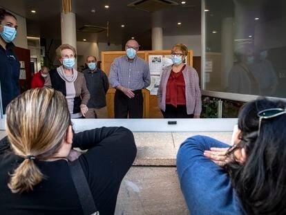 Familiares de los residentes del centro de mayores de Velluters observan a los usuarios desde la ventanas.