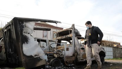 Un policía observa los destrozos provocados por manifestantes frente a la municipalidad de Ercilla, en la Araucanía chilena, el 2 de agosto de 2020.