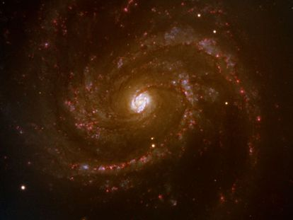 """La galaxia Messier 100 o M100 es uno de los 110 objetos catalogados por Charles Messier (1730-1817). Las galaxias son denominadas por los astrónomos los """"ladrillos del Universo"""", ya que se agrupan en grupos """"jerárquicos"""", cada uno de ellos con más miembros que el anterior, como son los cúmulos, y supercúmulos, que forman la estructura a gran escala del Universo."""