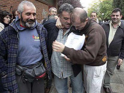 Dos trabajadores de Caballito se abrazan emocionados, ayer, tras la firma del acuerdo con la empresa que ha puesto fin a los dos años de huelga.