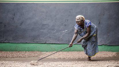 Una mujer seca semillas en Ghana.