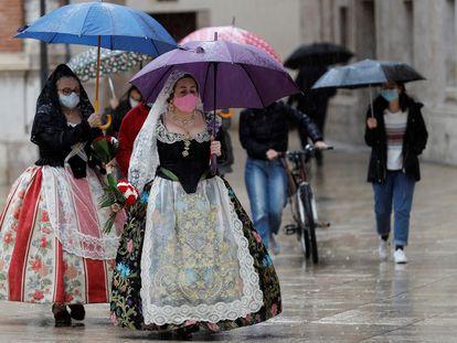 Dos falleras se protegen de la lluvia, este viernes en Valencia.