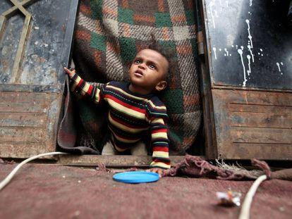 Un niño yemení desplazado desde Hodeida por la guerra gatea en la puerta de la choza de Sanaa, la capital del país, donde se ha refugiado su familia, en Sanaa, Yemen.