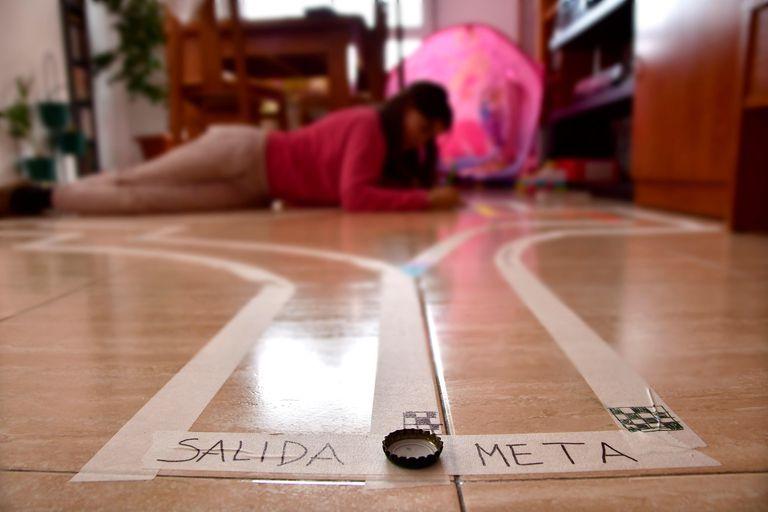 Una niña juega en una pista de chapas montada en su casa de Almería.
