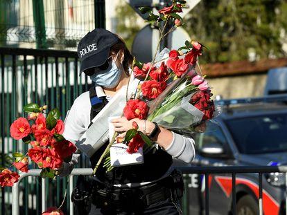 Una agente recupera flores dejadas en recuerdo de la funcionaria de policía asesinada el viernes en Rambouillet, en las afueras de París, en el último atentado terrorista en Francia
