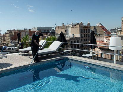 Un empleado realiza tareas de mantenimiento en la piscina de un hotel de Barcelona, este miércoles.
