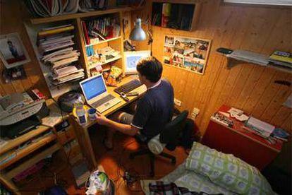 Un chico utiliza el ordenador en su habitación.