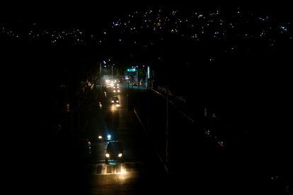 Los carros se abren paso por una calle obscura en una de las colonias de la periferia del Puerto de Acapulco.