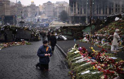 Un hombre se arrodilla en la plaza de la Independencia de Kiev, donde  murieron decenas de manifestantes.