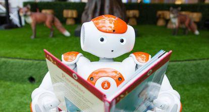 Un robot lee un libro durante una demostración de inteligencia artificial para niños en Londres.