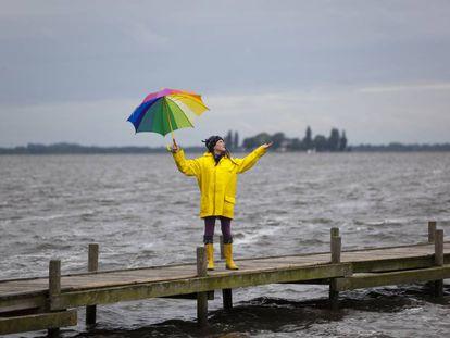 Una mujer con un chubasquero amarillo y un paraguas se protege de la lluvia en Steinhuder Meer, Alemania.