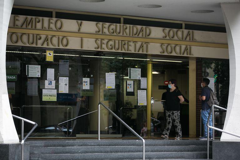 Varias personas esperan en las puertas de la oficina de Empleo y Seguridad Social de Barcelona.