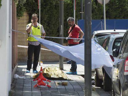 Dos 'mossos', junto al cadáver de un hombre asesinado en el centro de Lleida, en junio.