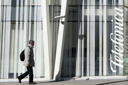 Un hombre pasa junto a la sede de Telefónica, en Barcelona.
