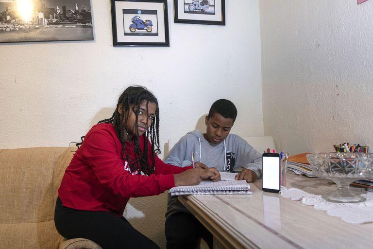 Paula y James Lee en su casa con el móvil al que su madre les manda capturas de pantalla con las tareas escolares que les ponen sus profesores en Castellón.