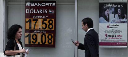 Mexicanos caminan frente a un banco con la cotización del peso mexicano, el pasado junio.