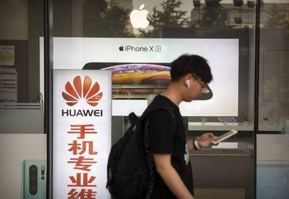Un hombre camina junto a una tienda con anuncios de Huawei y Apple, en Pekín, el pasado viernes.