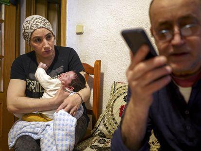 Rachid El Yagoubi trata de evitar que les desahucien mientras su mujer, Fátima Maknassi, le observa, con el cuarto hijo de ambos, Amir, de un mes, en los brazos.