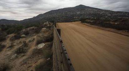 Muro en Tecate. Al fondo Cuchumá, cerro sagrado de los Kumiai