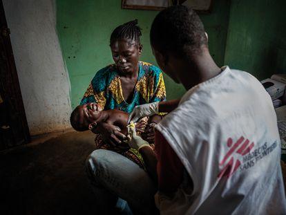 Un trabajador humanitario de MSF atiende a un niño en Bouca, República Centroafricana, en 2013.