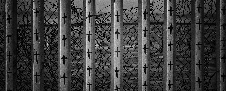 Cruces pintadas sobre el muro fronterizo representando a los migrantes fallecidos en su intento por cruzar.