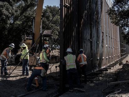 Trabajadores levantan el nuevo muro fronterizo en el desierto de Baja California.