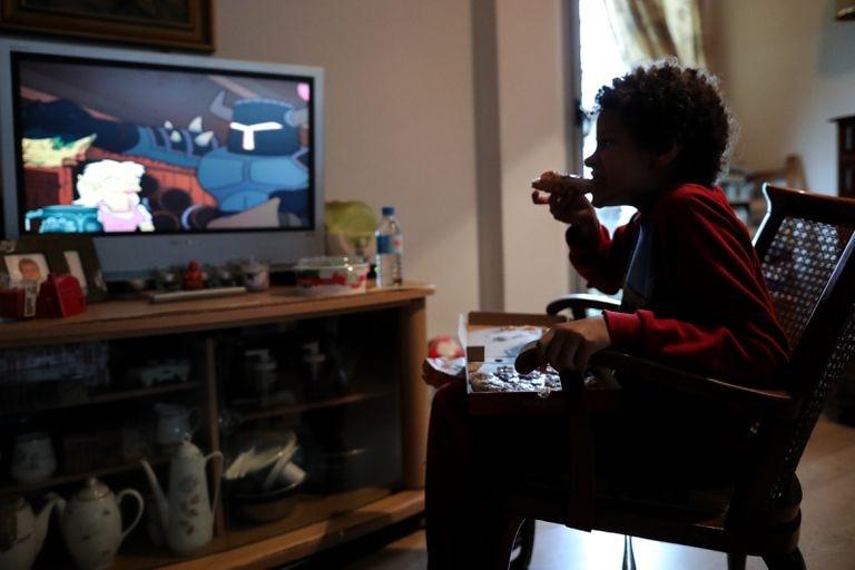 Un niño come un trozo de pizza en su casa en Madrid durante el confinamiento.