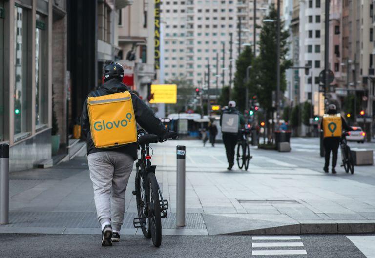 Dos repartidores de Glovo y otro de Deliveroo caminan por la Gran Vía de Madrid, en abril.