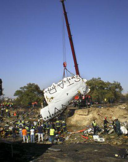 Una grúa levanta parte del fuselaje de la aeronave.