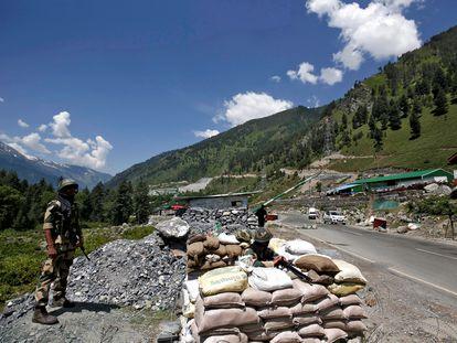 Un soldado indio hace guardia en un puesto de control en una carretera de camino a una de las áreas fronterizas en disputa con China