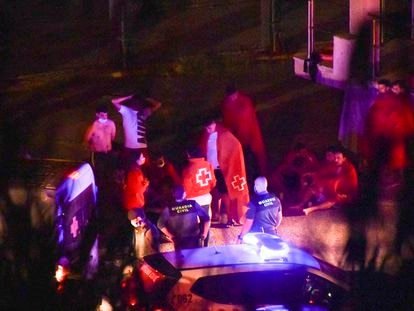 Varios miembros de la Guardia Civil y voluntarios de Cruz Roja atienden a un grupo de marroquíes en Ceuta.