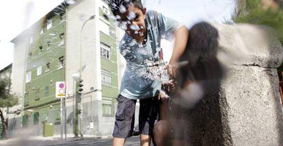 Un niño juega con el agua de una fuente en el barrio de San Blas, en Madrid.