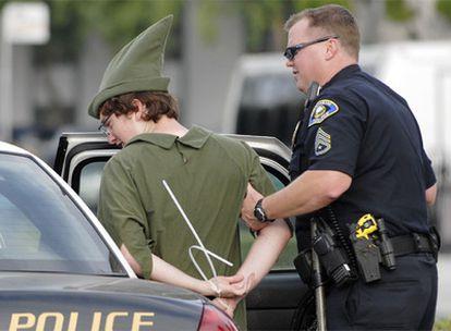 Un policía de la localidad de la localidad de Anaheim detienen a un trabajador disfrazado del héroe creado por James Matthew Barrie