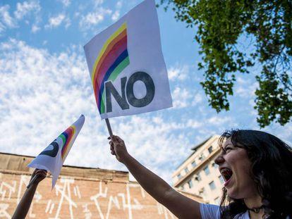 Una mujer porta una bandera de repudio a Pinochet a 30 años del plebiscito que puso fin a la dictadura.