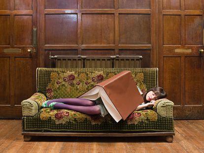 Una adolescente durmiendo con un gran libro sobre ella.