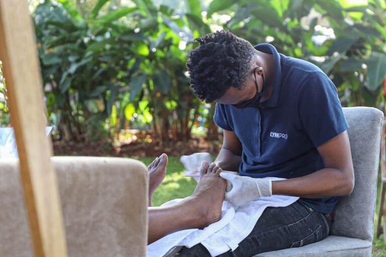 Un trabajador de Lynk, le hace la pedicura a una clienta en Kenia.