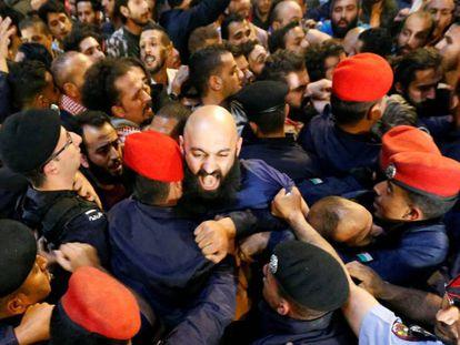 Policías chocan con manifestantes junto a la oficina del primer ministro, el domingo en Ammán.