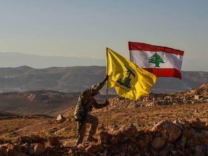 Un miliciano de Hezbolá planta las banderas libanesa y de la milicia tras expulsar a Al Nusra de los arreales de la localidad libanesa de Arsal