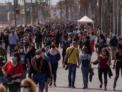 Cientos de personas caminan por el paseo marítimo de la Barceloneta, en Barcelona, este sábado.