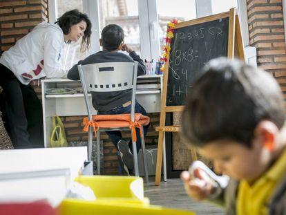 Una madre ayuda a sus hijos confinados en casa a hacer las tareas durante una cuarentena escolar en Madrid.
