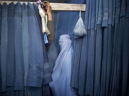 Una afgana espera en el probador de una tienda para probarse un burka en Kabul, Afganistán, el 11 de abril de 2013.