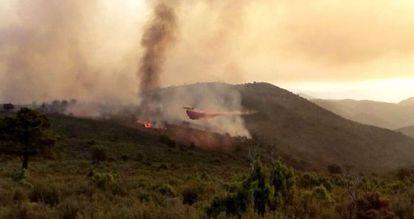 Un helicóptero trabaja en el incendio de Montán (Castellón).