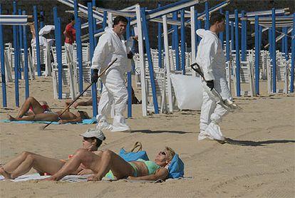 Varias personas toman el sol en la playa de La Concha, en presencia de operarios de limpieza del chapapote.