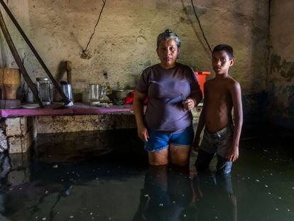 A woman and her son pose inside their flooded house in San Felix, Bolivar state, Venezuela, on August 10, 2018. - The Orinoco river floods have damage houses, crops and generate a potential outbreak to diseases for which medicines are lacking. The floods affect eight states, according to the government. (Photo by William R. Urdaneta / AFP)