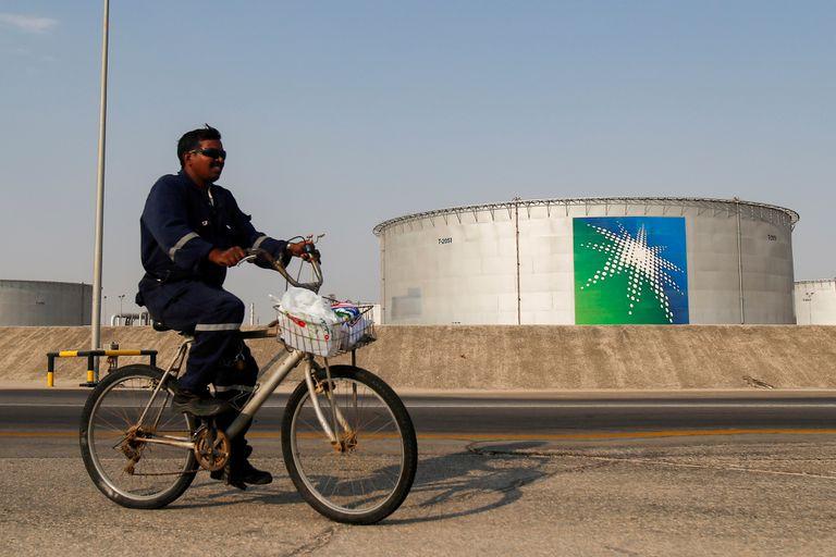 Un empleado pasa en bicicleta cerca de un tanque de petróleo de Aramco, la petrolera estatal saudí.