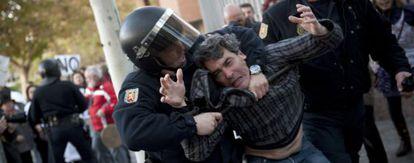 Efectivos de la policía detienen a uno de los asistentes a la protesta.
