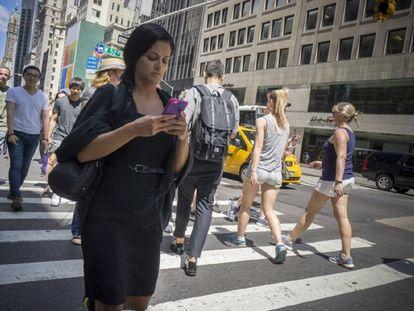 Una mujer mira el móvil mientras cruza la Quinta avenida de Nueva York.