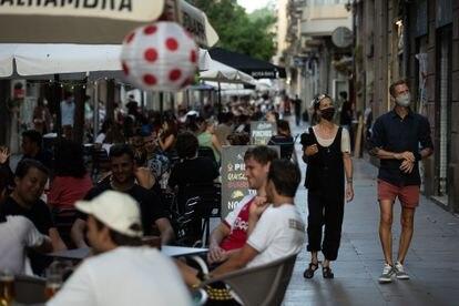 Dos personas pasean por una calle llena de terrazas en el barrio barcelonés del Poblesec