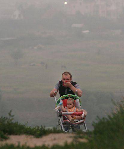 Un hombre se cubre la boca con un pañuelo mientras empuja el carrito de su hija a unos 30 kilómetros de Moscú.